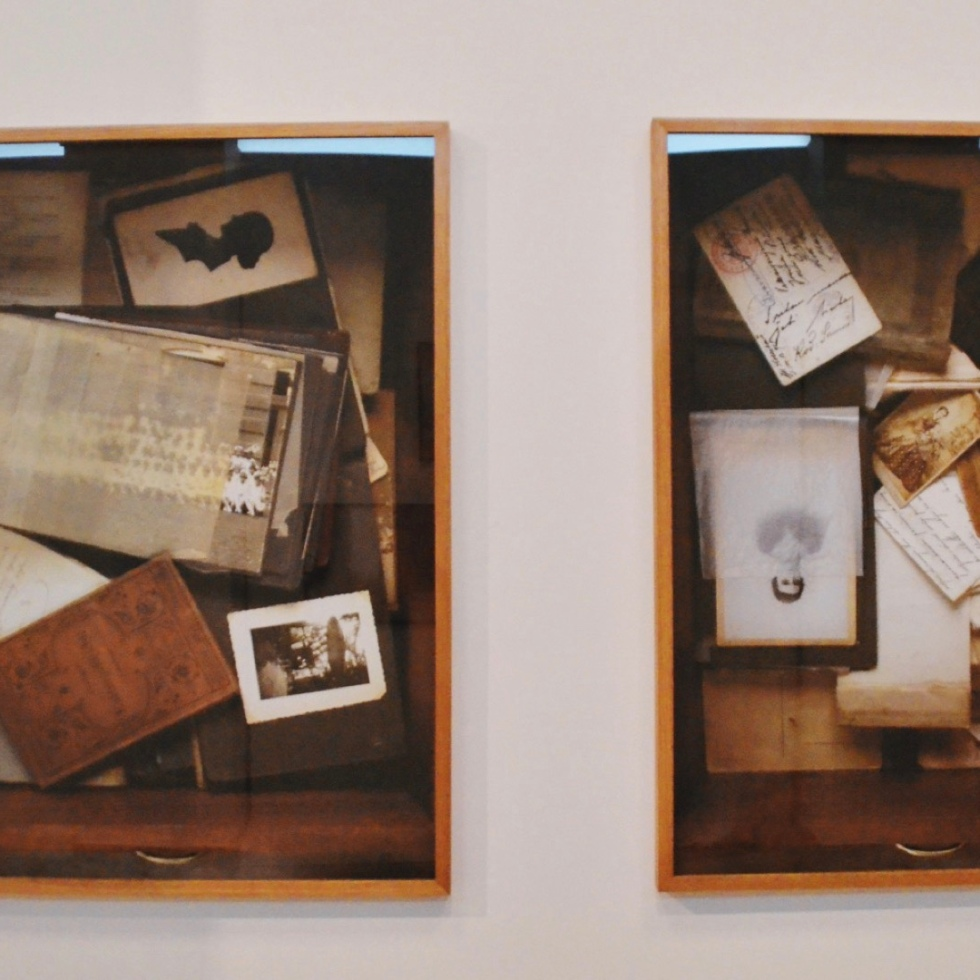 a collection of photographs and images in a glass case hung on a wall